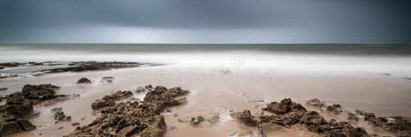 Abbellisca l'immagine lunga dell'esposizione di panorama delle rocce e della spiaggia sabbiosa fotografie stock libere da diritti