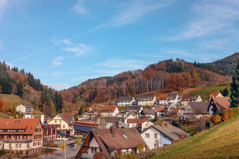 Abbellisca la campagna di autunno con le fattorie di legno sulla collina verde e sulle montagne irregolari nei precedenti ~ vista immagini stock libere da diritti