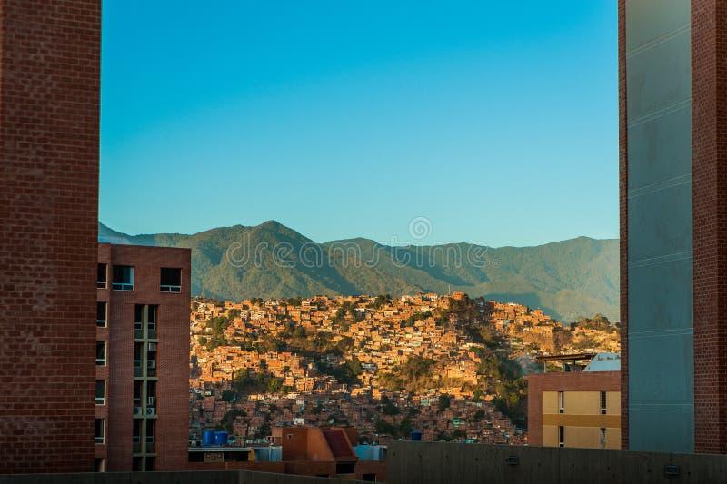 Abbellisca la vista della città di Caracas durante il tramonto con cielo blu ed avila fotografia stock