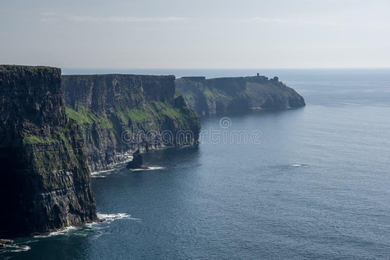 Abbellisca la vista delle scogliere di Moher e del mare blu scuro sul chiaro sole immagini stock