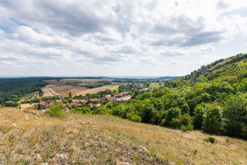 Abbellisca la vista di piccoli villaggio, prato ed agricoltura Foresta dalla destra con gli alberi verdi, cielo blu, nuvole immagini stock libere da diritti