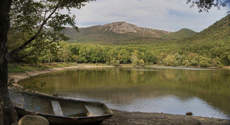 Abbellisca la vista in lago, montagne e vecchia barca immagini stock