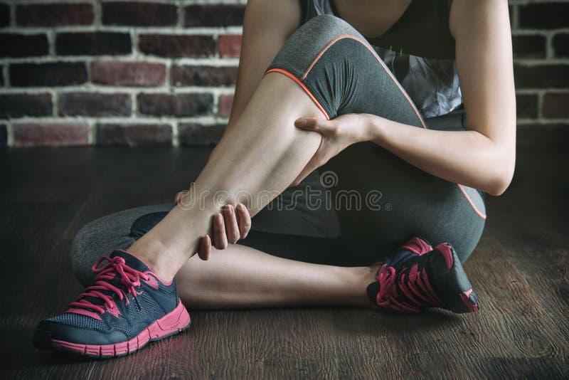 Abbia un crampo di gamba nell'addestramento di esercizio di forma fisica, stile di vita sano fotografia stock