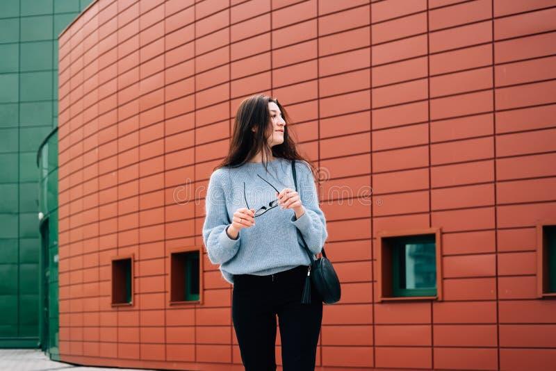 Abbigliamento casual d'uso della bella e donna felice che posa nella via della città su fondo urbano moderno immagini stock