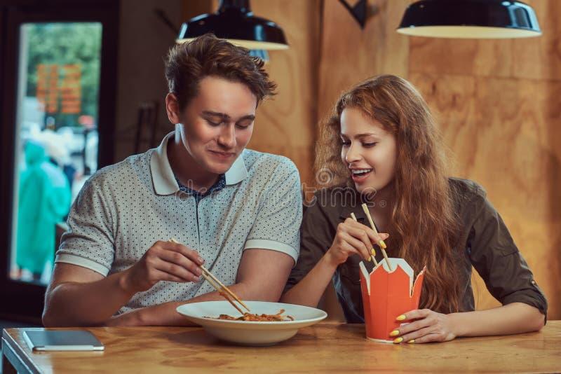 Abbigliamento casual d'uso delle giovani coppie che mangia le tagliatelle piccanti in un ristorante asiatico fotografia stock libera da diritti