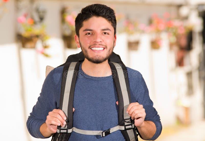 Abbigliamento casual d'uso e zaino del giovane uomo felice che posano per la macchina fotografica, sorridenti, ambiente del giard immagini stock libere da diritti