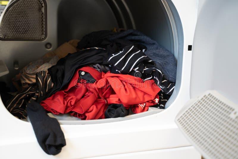 Abbigliamento che si siede dentro di un essiccatore della lavanderia, pronto ad essere piegato immagini stock
