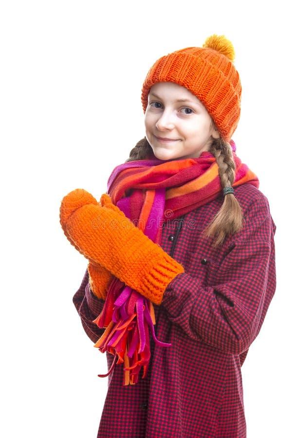 Abbigliamento di inverno dei bambini ed idee di feste Bambina caucasica sorridente in Beanie, sciarpa e guanti arancio Sopra bian fotografia stock libera da diritti