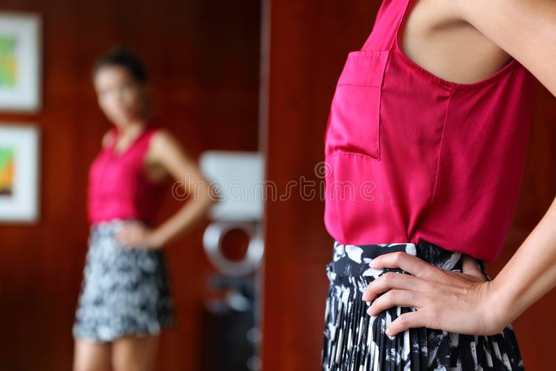 Abbigliamento di prova della donna che esamina lo specchio immagini stock