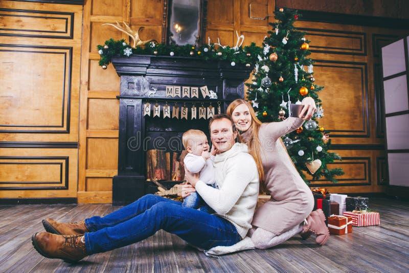 Abbildung kann als Hintergrund benutzt werden junge Familie mit blondem Jungen von einem Jahr sitzt auf Bretterboden gegen Hinter lizenzfreies stockfoto