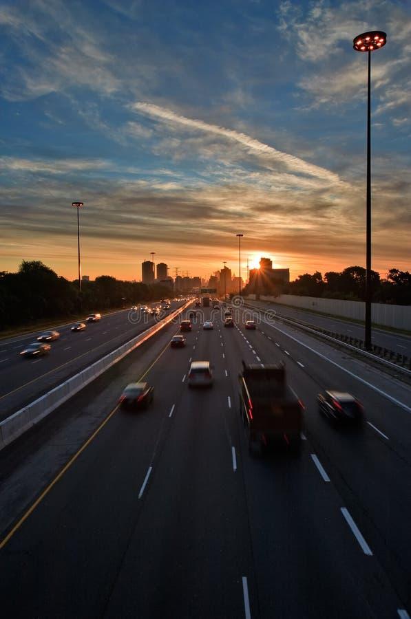 Abbonati che provano a battere il traffico al tramonto immagine stock