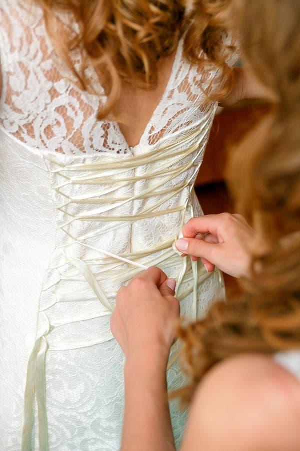 Abbottonare il vestito da sposa della sposa Fine in su fotografie stock