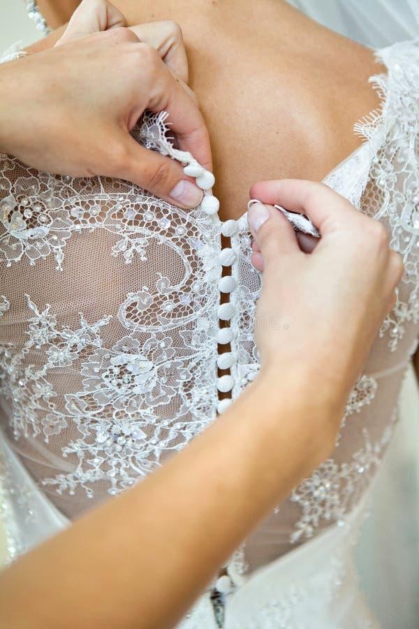 Abbottonare il vestito sulla sposa, dettagli di bello vestito da sposa dal pizzo fotografia stock