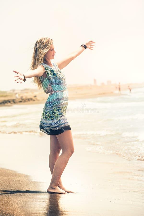 Abbracci il mare, donna di sogno della spiaggia Pace e libertà immagini stock