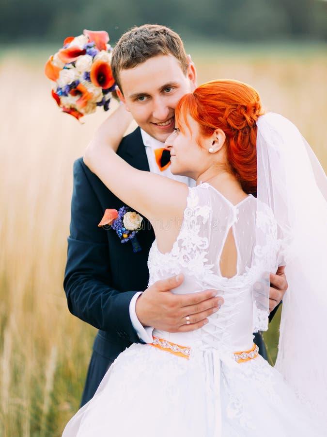 Abbracciando sul giacimento di grano al giorno soleggiato La bella sposa del redhair con lo sposo bello gode della luna di miele fotografie stock