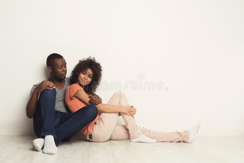 Abbracciare afroamericano delle coppie, sedentesi sul pavimento fotografia stock libera da diritti