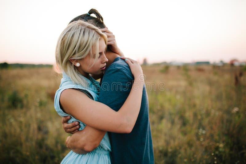 Abbracciare delle coppie all'aperto nel campo immagine stock