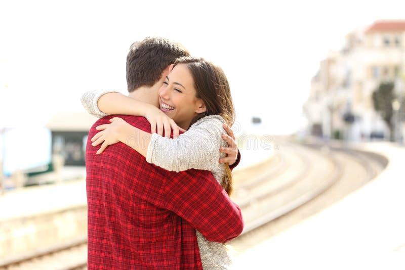 Abbracciare delle coppie felice in una stazione ferroviaria fotografia stock libera da diritti