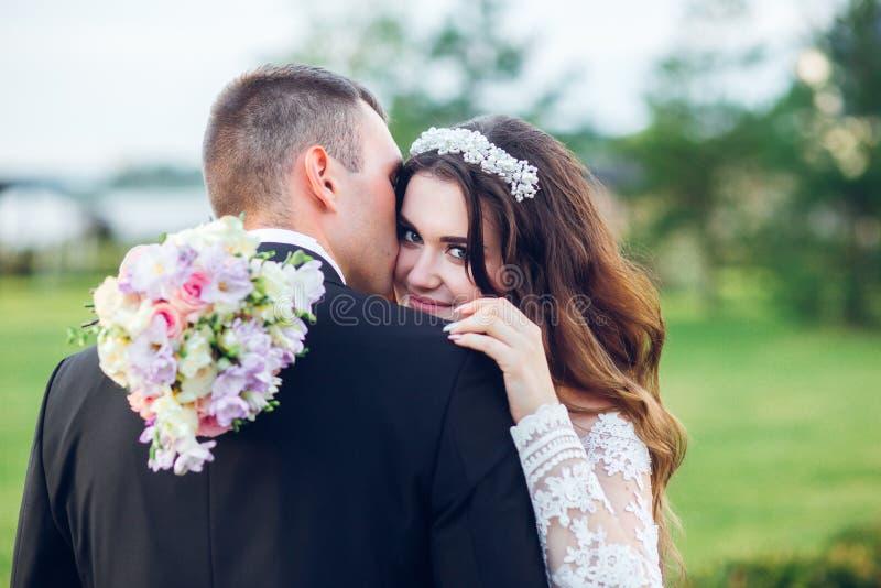 Abbracciare sorridente stupefacente delle coppie di nozze Sposa graziosa e sposo alla moda fotografia stock libera da diritti