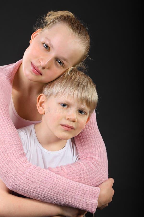 Abbraccio della sorella e del piccolo fratello immagini stock