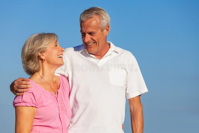 Abbraccio di camminata delle coppie senior felici in cielo blu fotografia stock libera da diritti