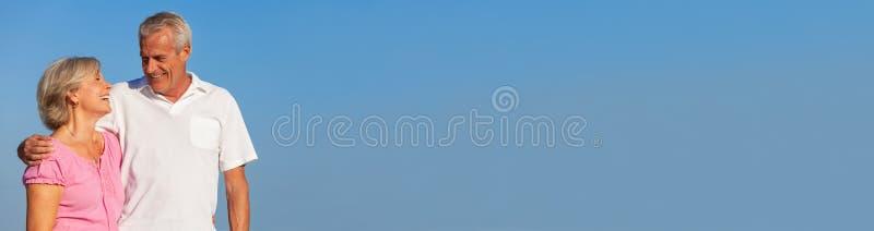 Abbraccio di camminata delle coppie senior felici nel panorama del cielo blu fotografia stock