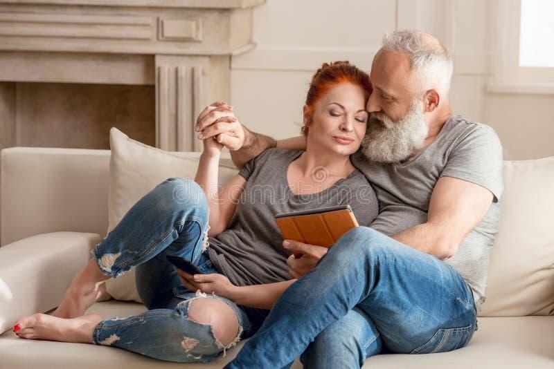 Abbraccio di seduta delle coppie mature e per mezzo della compressa digitale immagini stock