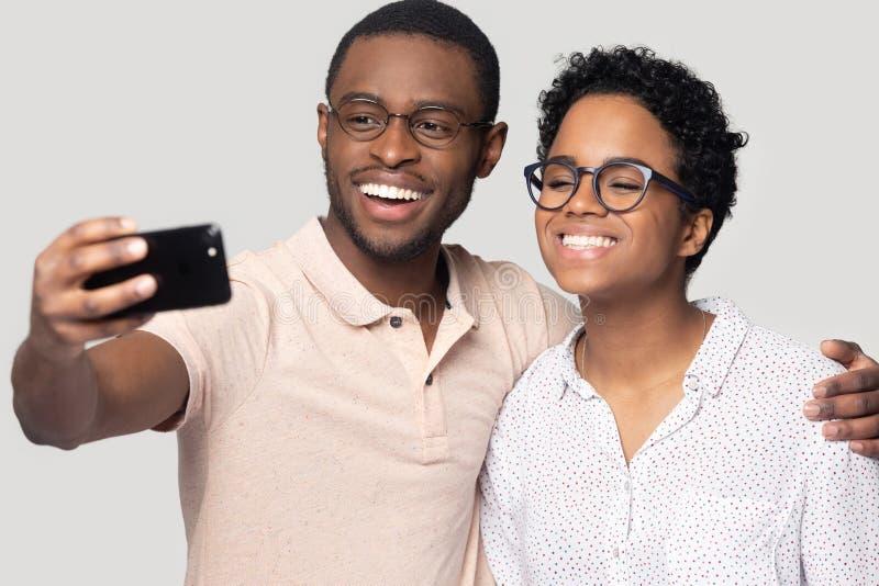 Abbraccio etnico sorridente delle coppie che posa insieme per il selfie fotografia stock libera da diritti