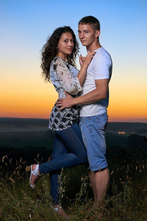 Abbraccio romantico delle coppie al tramonto, al bello paesaggio ed al cielo giallo luminoso, concetto di tenerezza di amore, gio fotografia stock libera da diritti