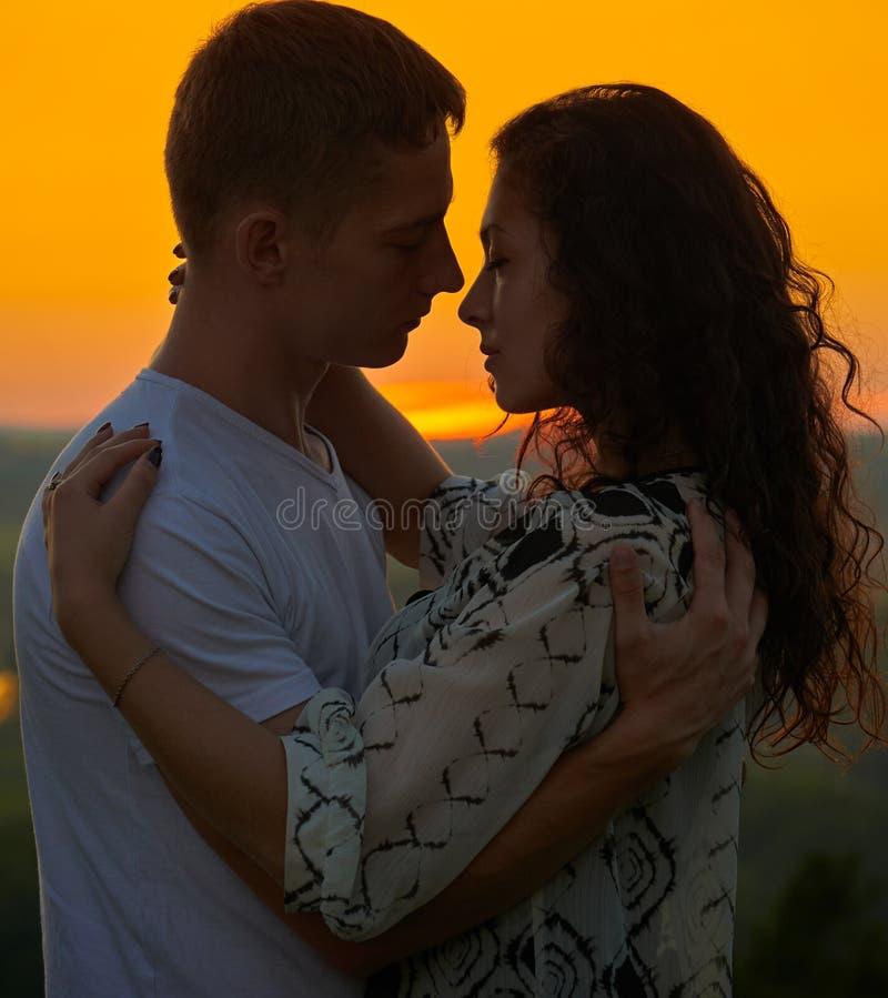 Abbraccio romantico delle coppie al tramonto su paesaggio all'aperto e bello e sul cielo giallo luminoso, concetto di tenerezza d fotografie stock libere da diritti