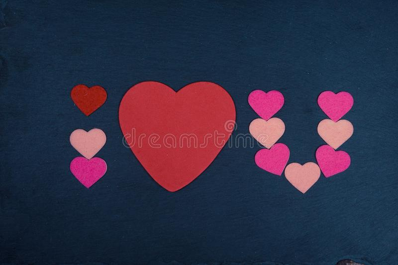 Abbreviated text I Love You with heart shape on chalkboard stock image