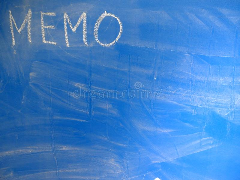 Abbreviation MEMO written on a blue, relatively dirty chalkboard by chalk. Located in the upper left corner of the image making. Space for some message or note royalty free stock photography