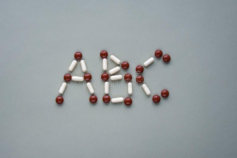 ABC é feito de comprimidos marrons e brancos da medicina em um fundo verde imagem de stock royalty free