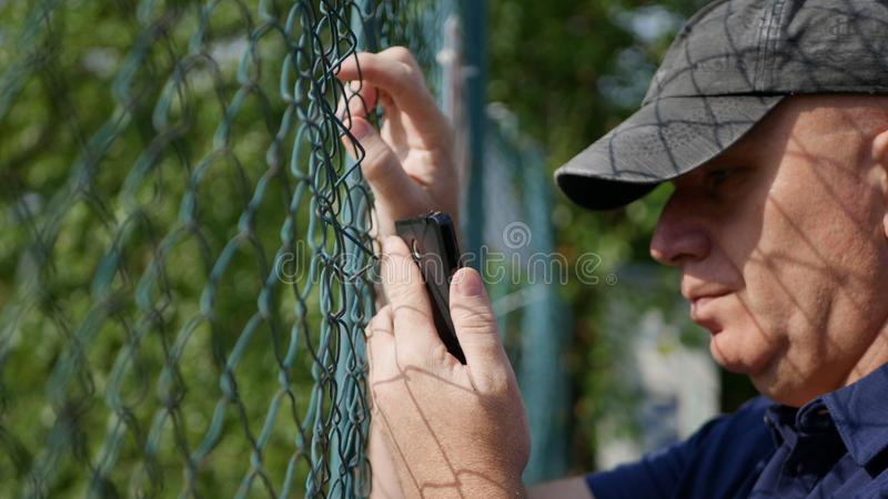 Man in Back of a Metallic Fence Reading a Text Using Smartphone. royalty free stock images
