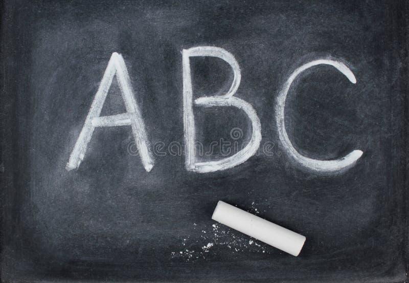 Abc- brieven en krijt op bord stock fotografie