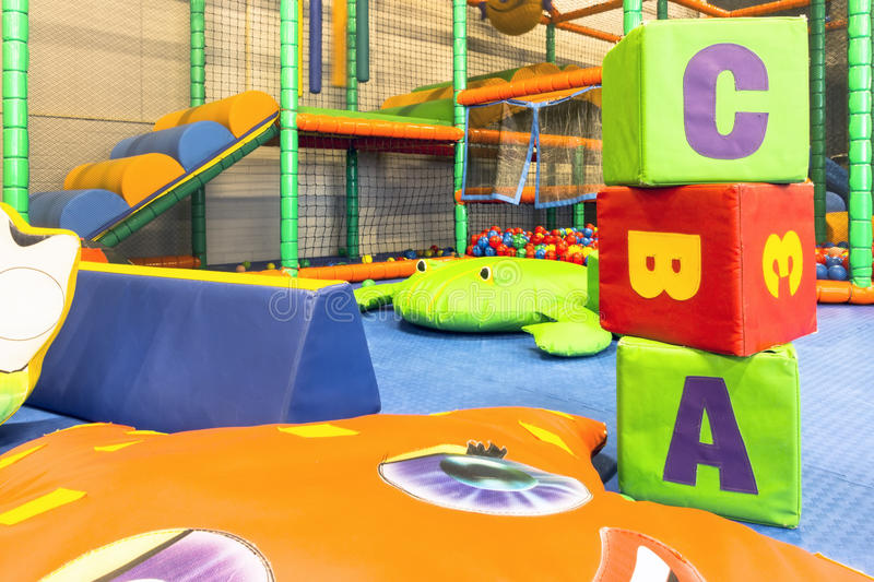 ABC cubes indoor playground. Entrance for kids with ball guns, bumpers, punching cylinder, slide, bridge, balls stock photos