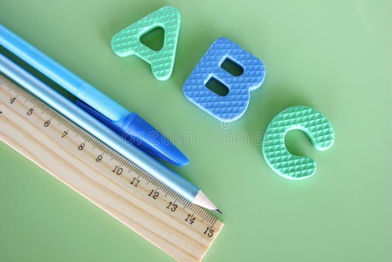 ABC - letras del alfabeto inglés en un fondo verde al lado de la pluma, del lápiz y de la regla foto de archivo libre de regalías