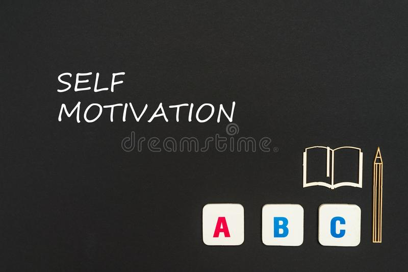 Abc letters and chipboard miniature on blackboard with text self motivation. Concept english school, text self motivation, abc letters, chipboard miniature book stock photography
