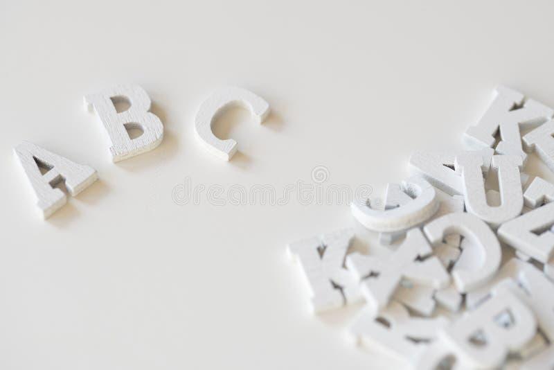 ABC pisać z białymi drewnianymi listami, przeciw białemu tłu zdjęcia stock