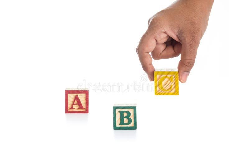 ABC pisze w kolorowych drewnianych abecadło blokach, ręce trzyma C odizolowywa na bielu i fotografia royalty free