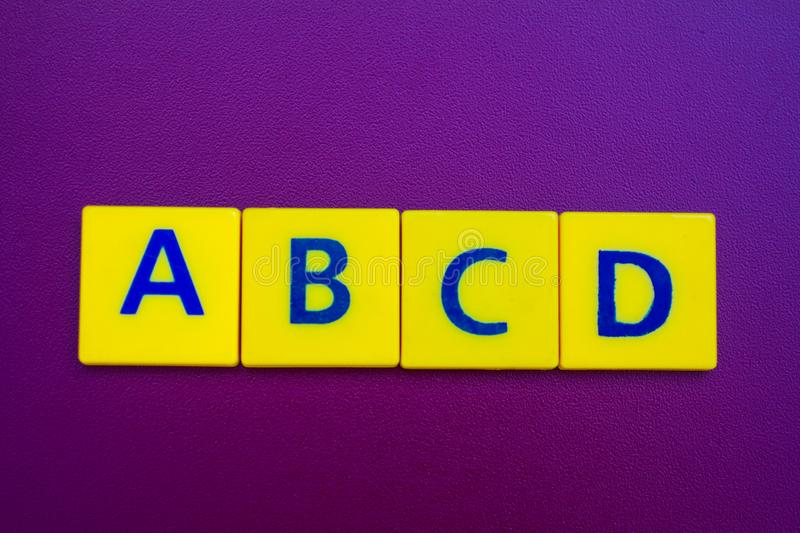 ABCD spelling on yellow plastic cubes royalty free stock images