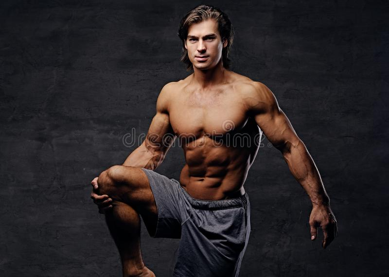 Abdominal male doing legs workouts. royalty free stock photography