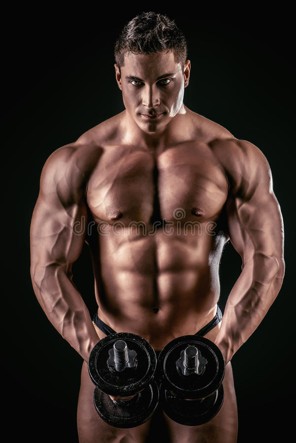 Abdominals. Portrait of a handsome muscular bodybuilder posing with dumbbells over black background royalty free stock photos