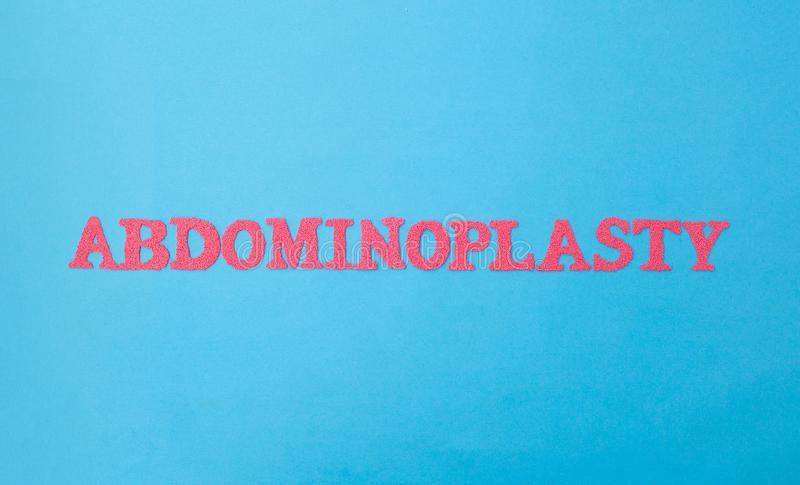 Abdominoplastie en lettres rouges sur fond bleu Le concept de correction des plis gras et de la cellulite sur image libre de droits