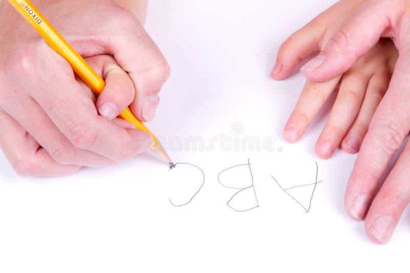 abecadła córki pomaga matka pisze obraz stock