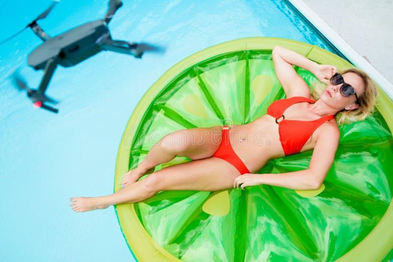 Abejón sobre la muchacha que toma el sol en piscina foto de archivo libre de regalías