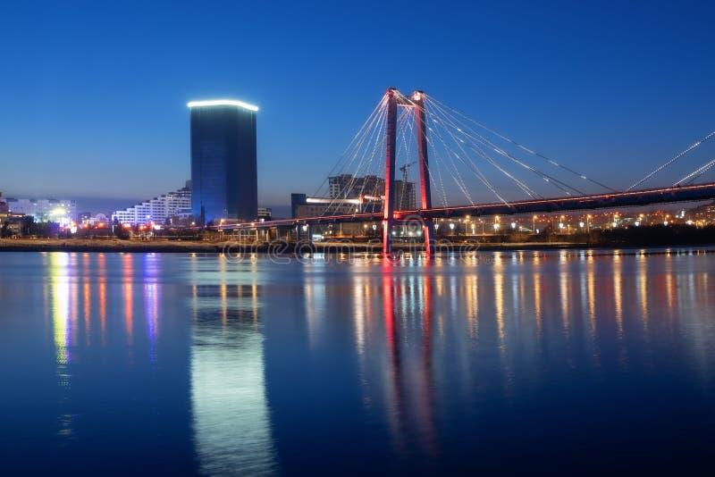 Abend und Nacht Krasnojarsk, Panoramanachtstadt Schrägseilbrücke in den hellen Lichtern St?dtische Landschaft lizenzfreie stockbilder