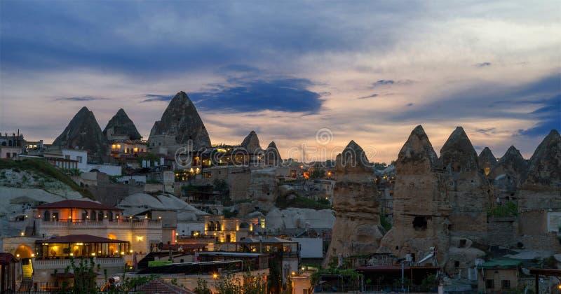 Abendansicht des Dorfs von Goreme in Cappadocia auf dem Hintergrund des natürlichen Geländes und des Abendhimmels lizenzfreie stockfotografie