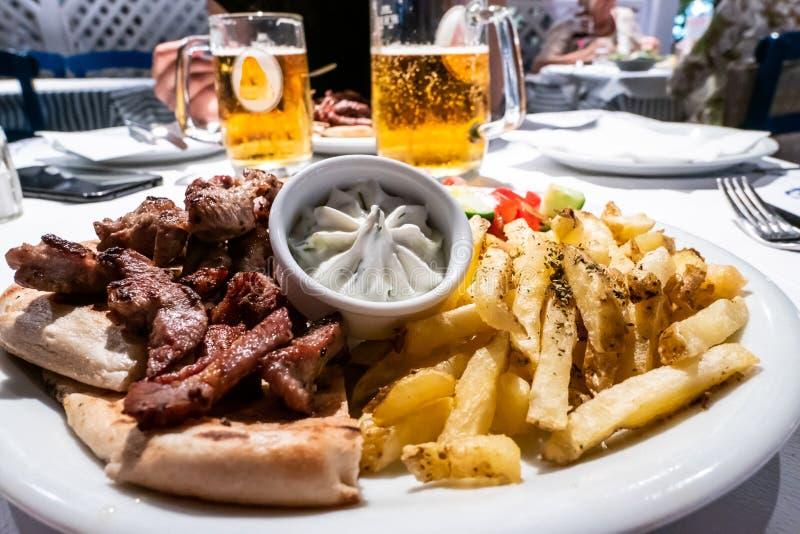 Abendessen bei Kamari, Santorini, griechischer Teller mit Pittabrotkreiselkompassen, berühmte Jogurtsoße stockfoto