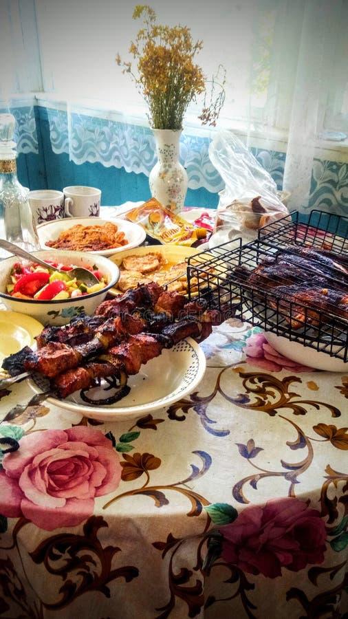 Abendessen im Dorf mit gegrilltem Fleisch, Huhn und Salat stockfotografie